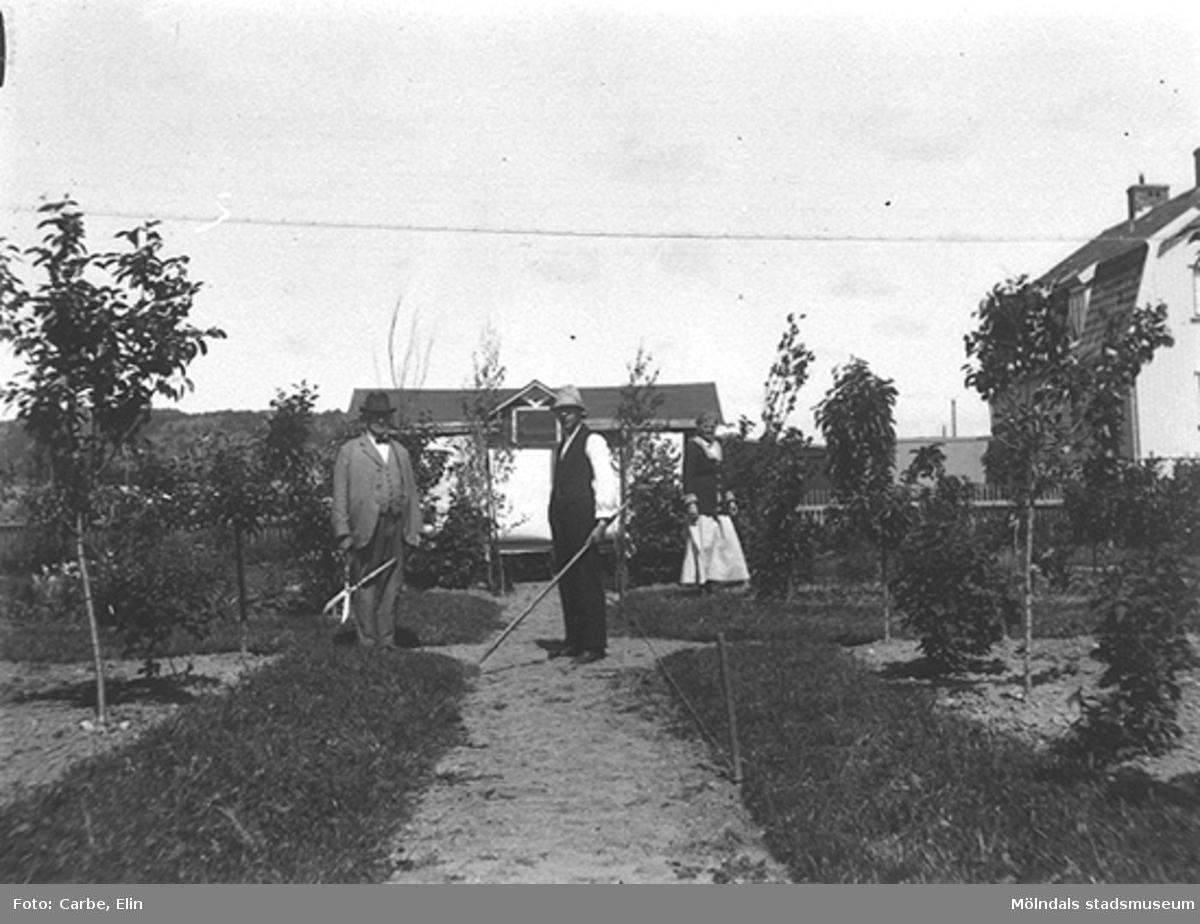 Tre personer står bakom huset i en trädgård. En av dessa kan vara K.A. Karlsson (som senare bytte namn till Carbe).