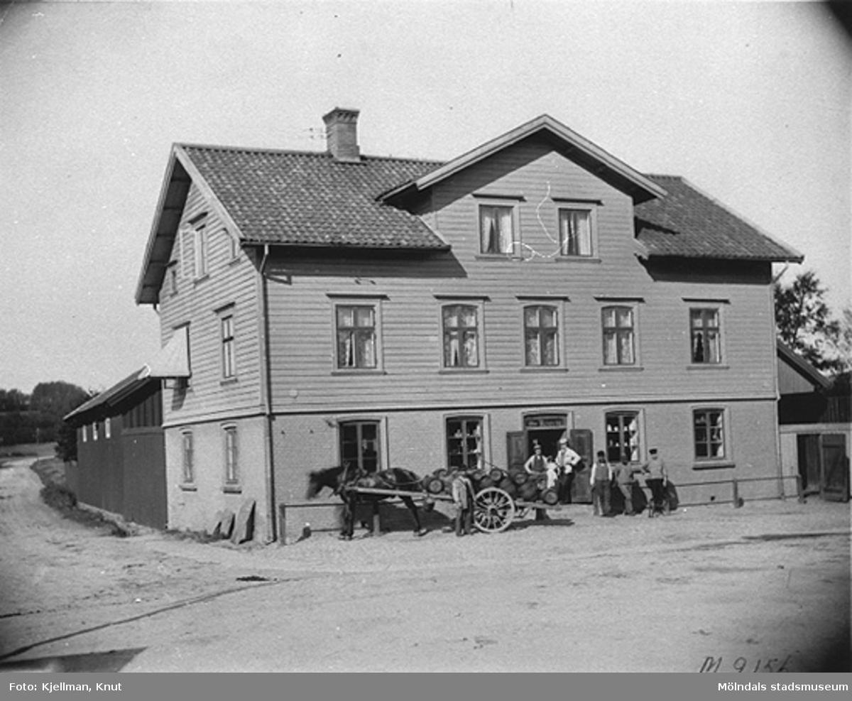Kennedys speceriaffär i hörnet Frölundagatan (Brogatan) och Göteborgsvägen 1, 1910-tal. Emiliedals bryggeri lastar av svagdricka.