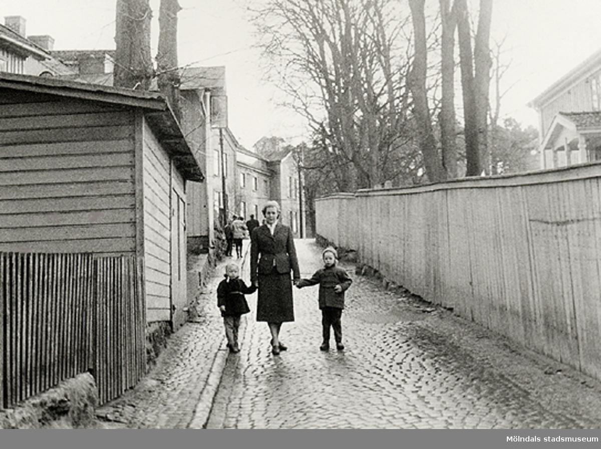 De promenerar i backen nedför Forsåkersgatan, år 1957. I bakgrunden till vänster ses den höga byggnaden som var Gamla sjukhuset, efter det polishus och senare Mölndals museum (Norra Forsåkersgatan 19).