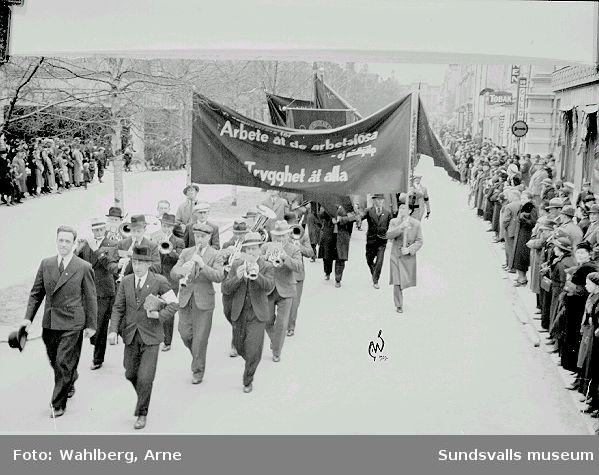 """1:a maj-demonstration på väg nedför Köpmangatan mot mötesplatsen på östra Hamnplan, 1927. Fotografiets banderolltexter, """"Arbete åt de arbetslösa - ej nödhjälp"""", """"Trygghet åt alla"""", anspelar på flera förhållanden. Till följd bl.a. av rationaliseringar inom produktionen så var många arbetare inom Norrlands skogsindustrier arbetslösa. Den statliga Arbetslöshetskommissionens dåligt betalda s.k. AK-arbeten ansågs bara fungera som en nödhjälp - man krävde deras avskaffande mot en större samhällelig insats mot arbetslösheten."""