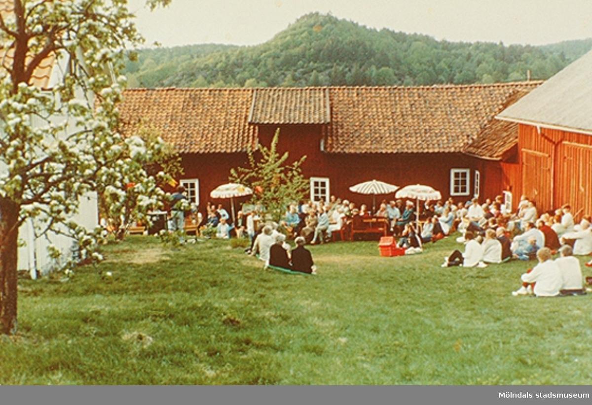 Människor sitter i gräset och på bänkar utanför Börjesgårdeen/Lindome Hembygdsgård. De lyssnar på ett uppträdande. Okänt årtal.