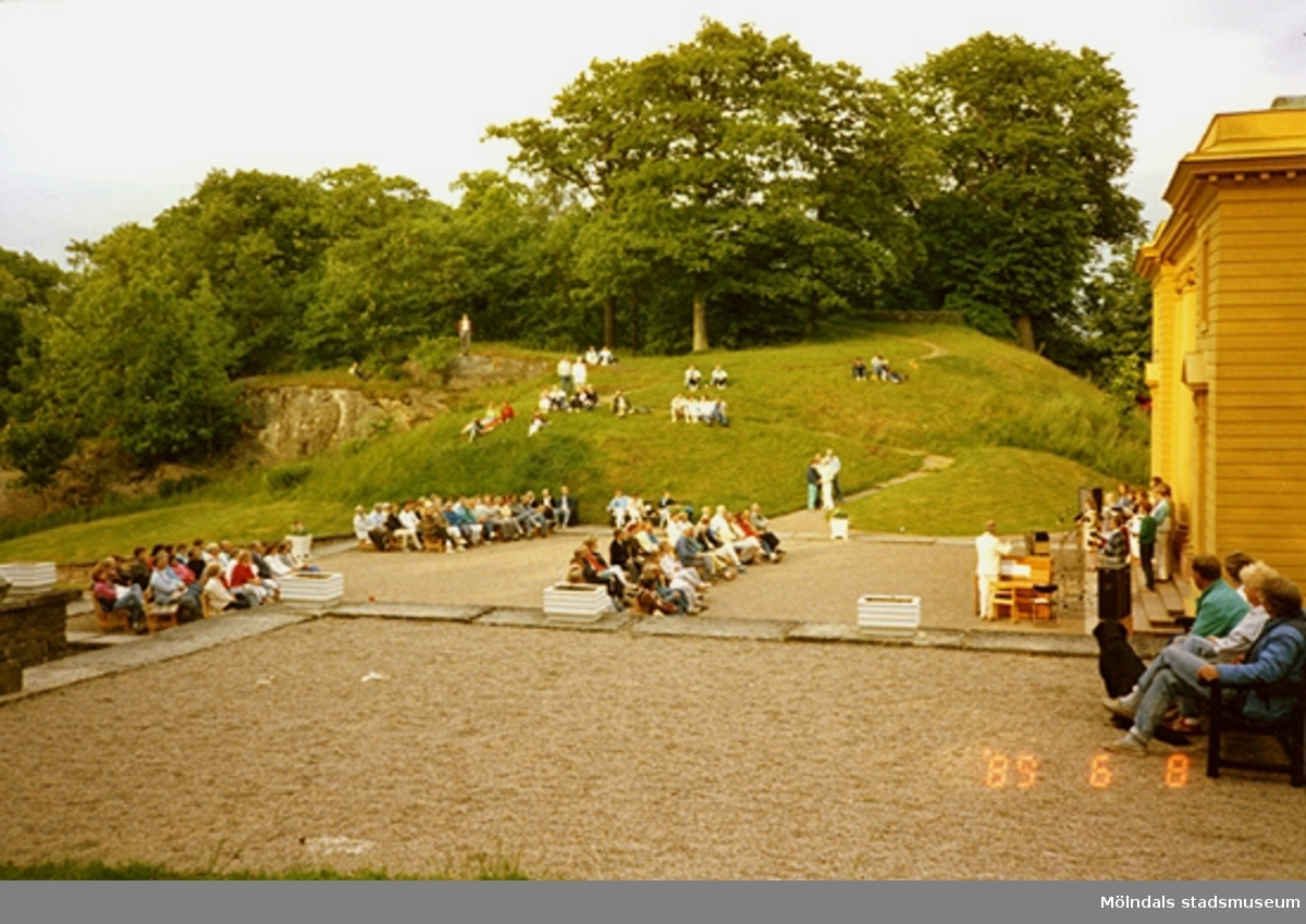 Publiken sitter i parken och lyssnar på musikunderhållning som pågår på scenen.