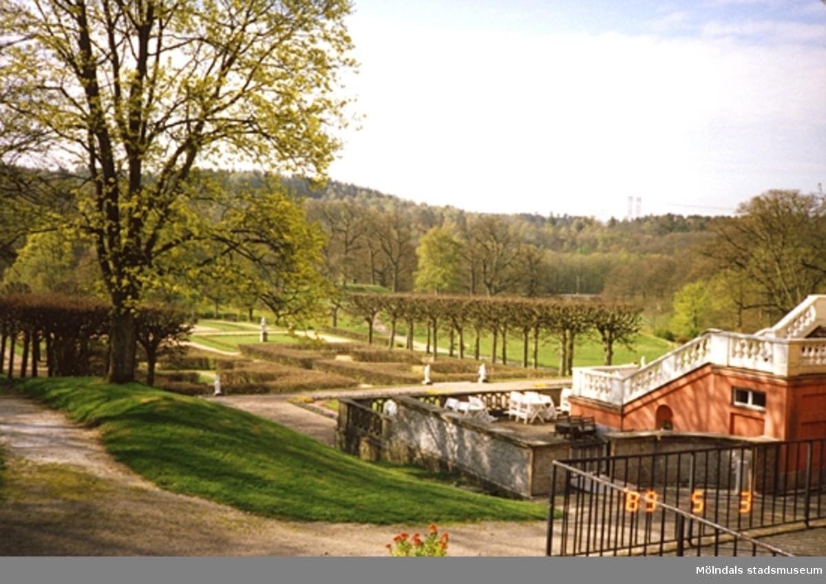 Vy från nordost mot parken, skogsbygden, slottstrappan och stenmuren. Till höger ser man en del av det staket som omgärdar köksgården.