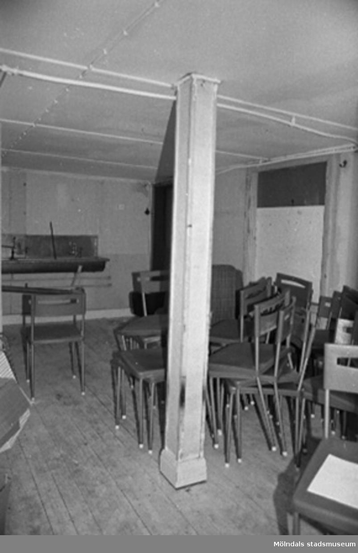 Interiör med stolar. Byggnadsdetaljer: Pelare och ledningar i taket.
