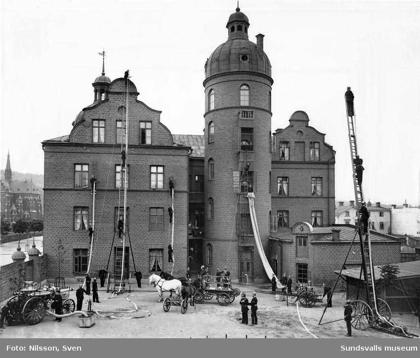 Gamla brandstationen. Brandredskapen demonstreras under ledning av brandchef Gustaf Hellgren som står längst ned till höger. Stora ångsprutan till vänster drogs av hästar.