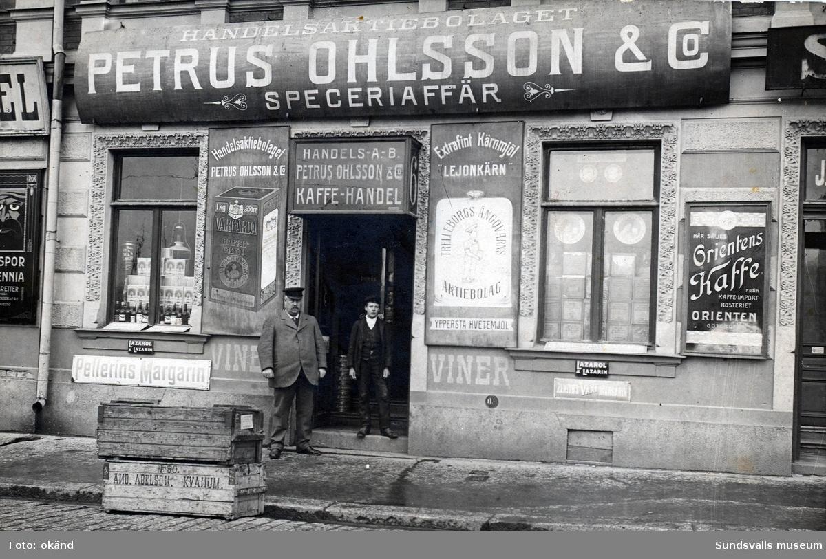 Petrus Ohlsson vid sin speceriaffär på Sjögatan 6. Springsjasen till höger heter Nils August Vallström. Butiksägaren Petrus Ohlsson var född 1856 i Alsen, Jämtland och kom till Sundsvall 1877 för att bedriva handel. Han avled 1944 i Sundsvall.