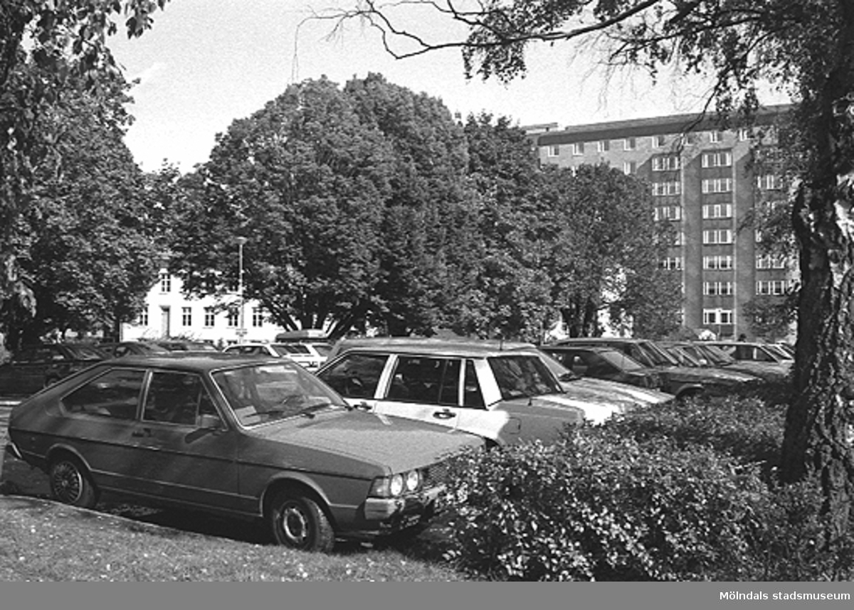 Parkeringsplats utanför R-husets (skymtar genom träden) södra sida. Mölndals sjukhus ses till höger i bakgrunden, år 1992.