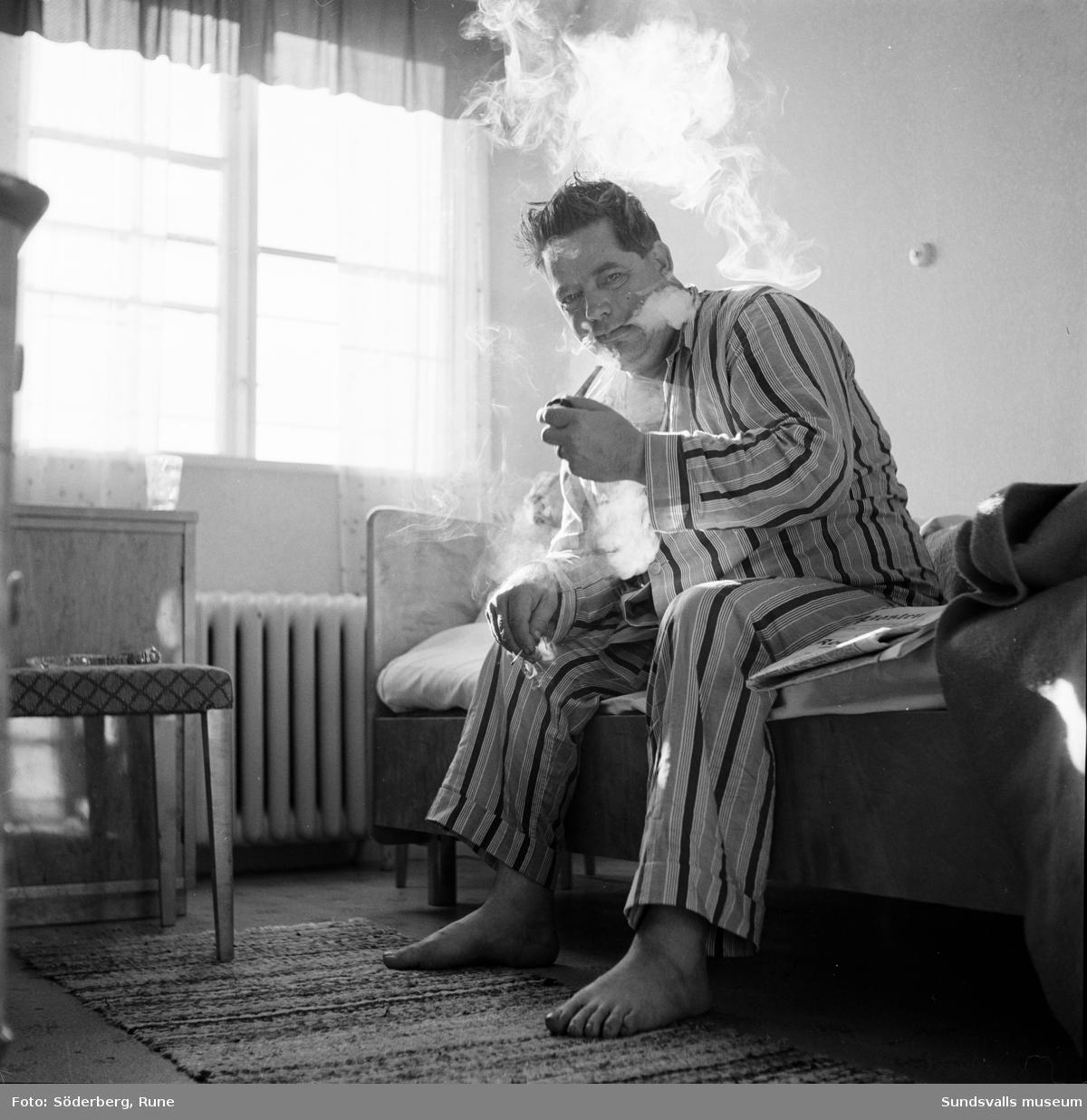Man i pyamas sitter på sängkanten och röker pipa.
