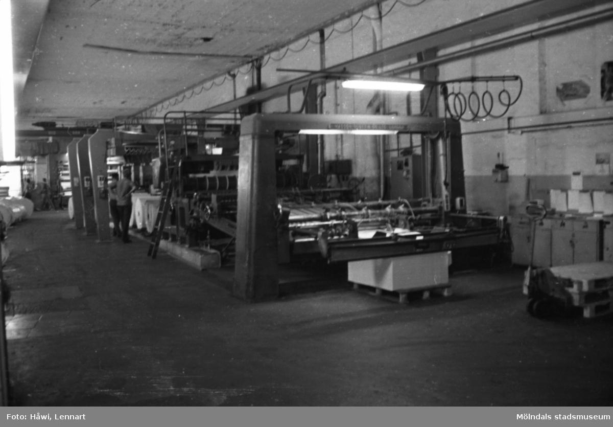Män i arbete vid maskin. Klipp 5 och klippta pappersark på pall. Byggnad 10. Papyrus i Mölndal, hösten 1970.