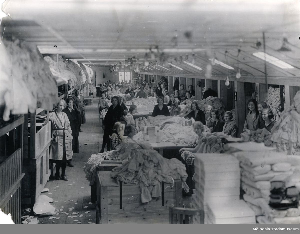 """Kvinnliga fabriksarbetare uppställda för fotografering i fabrikslokal på """"Strumpan""""."""
