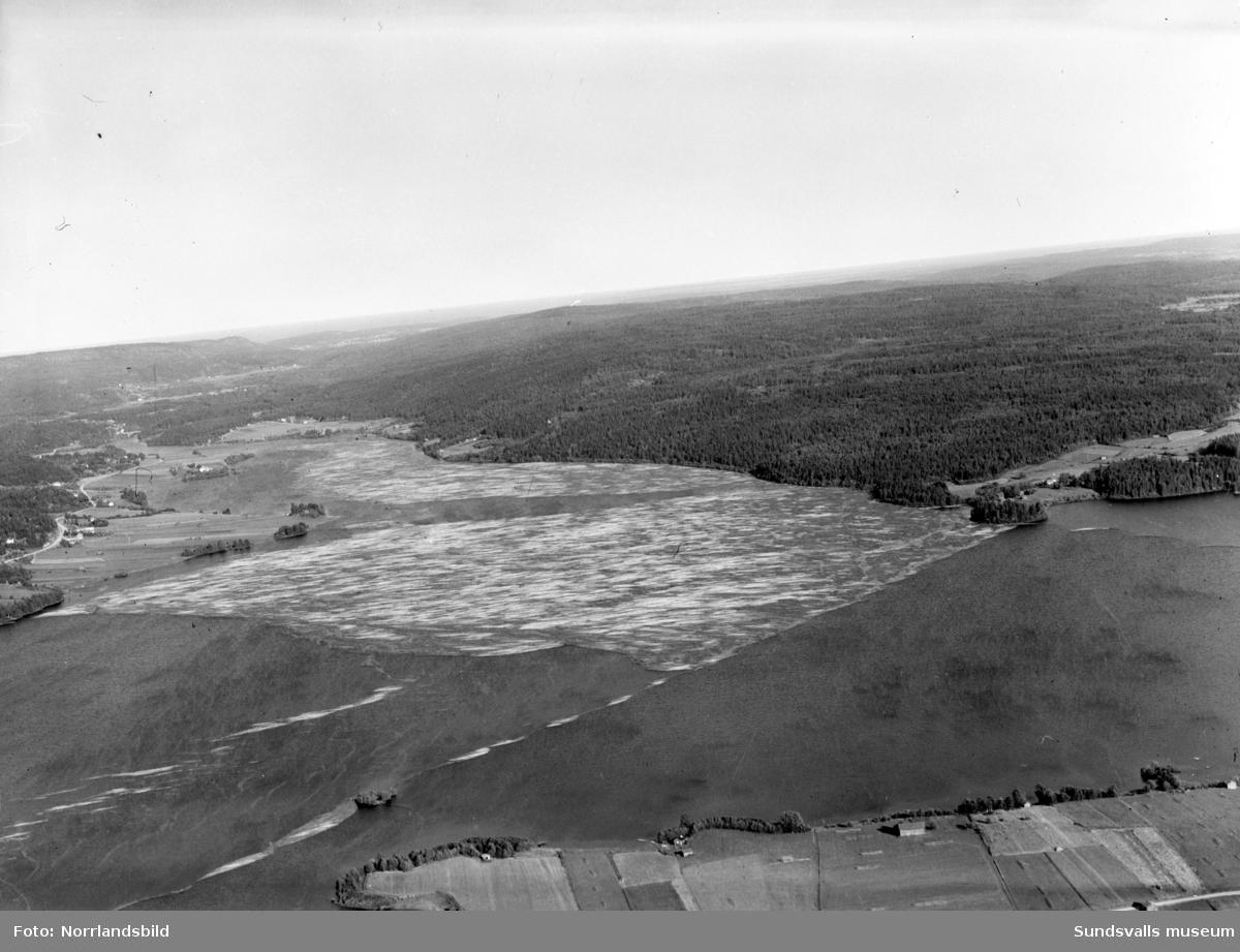 Flygfoton över Marmen som är fylld av timmer på väg ned mot kusten. På en av bilderna syns Attmars kyrka till vänster och Tuna kyrka till höger.