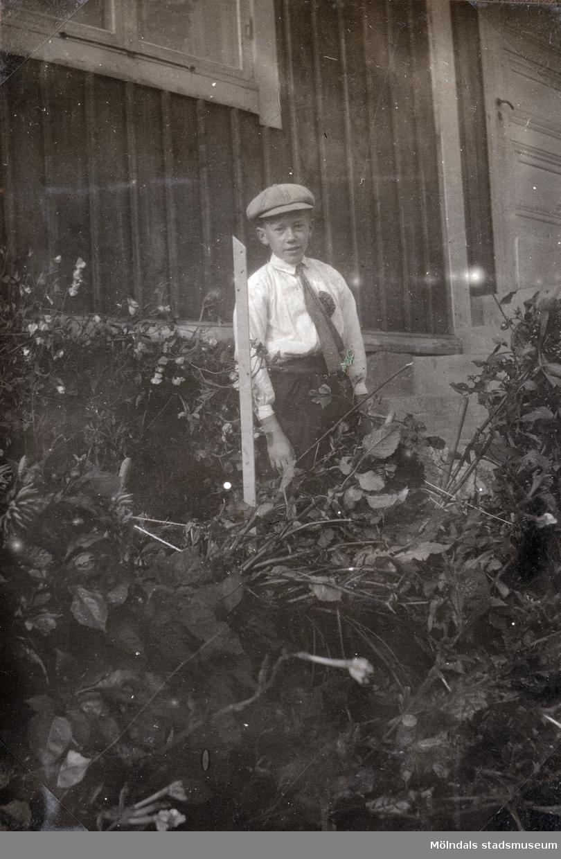 Åke Börjesson som pojke fotograferad i trädgården. Fotografi ur album som tillhört Åke Börjesson.