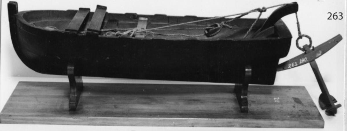 """Båtmodell Barkass, av trä, med anordning för utläggning och intagning av varpankare (Clippers patent). Modellen består av: barkass med 4 mastbänkar, 2 st taljor med 2 st block samt 1 st dävert och 1 st ankare (mm 263). Modellen är svartmålad. Modellen är defekt. Under modellstativet finns texten """"Tillverkad Januari 1981""""."""