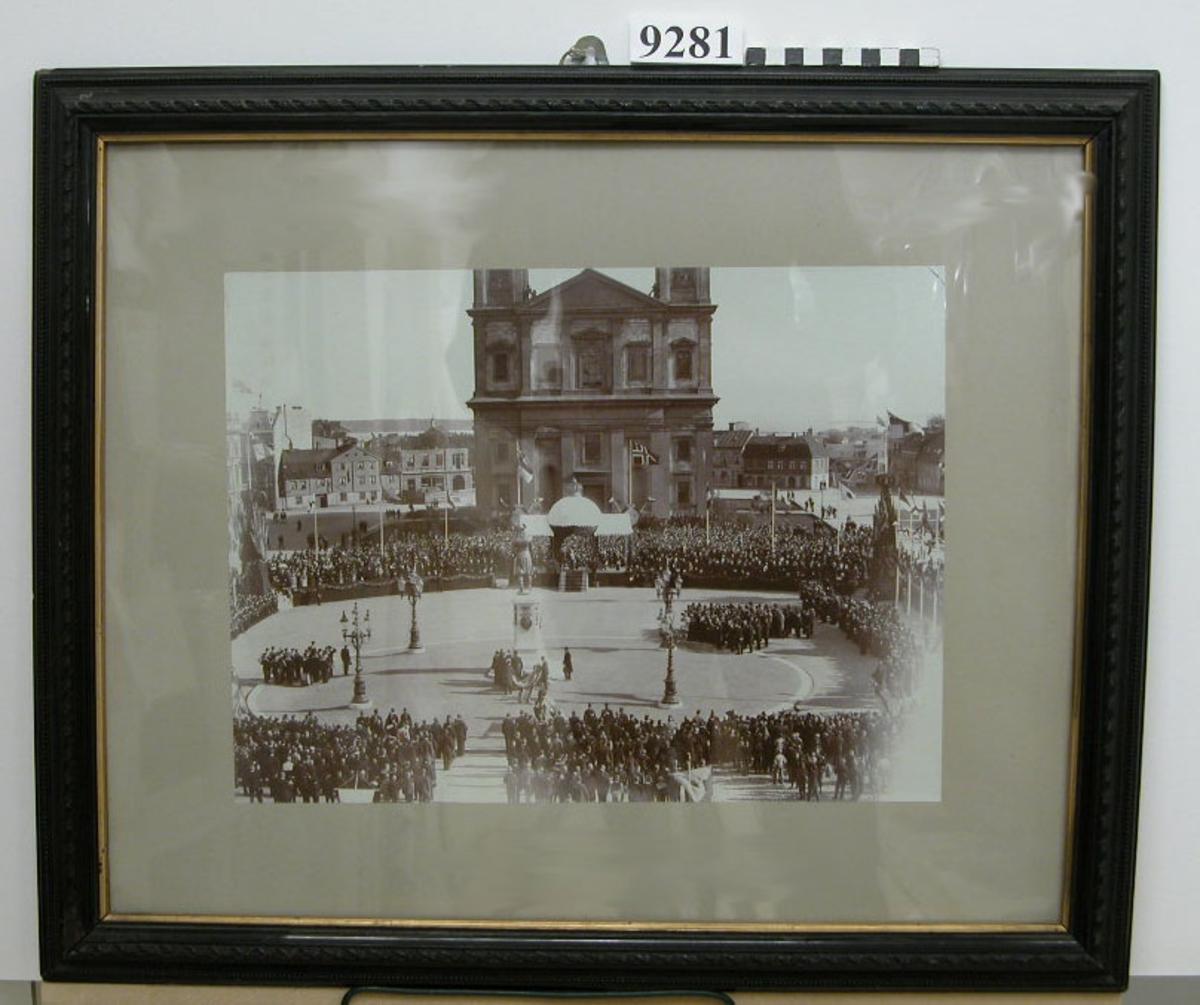 Fotografi inom glas och ram. Ramen av trä, svart med förgylld innerkant. Föreställer avtäckningen av Carl XI:e statyn å Karlskrona stortorg år 1897. (Dubblett finnes K 9152)