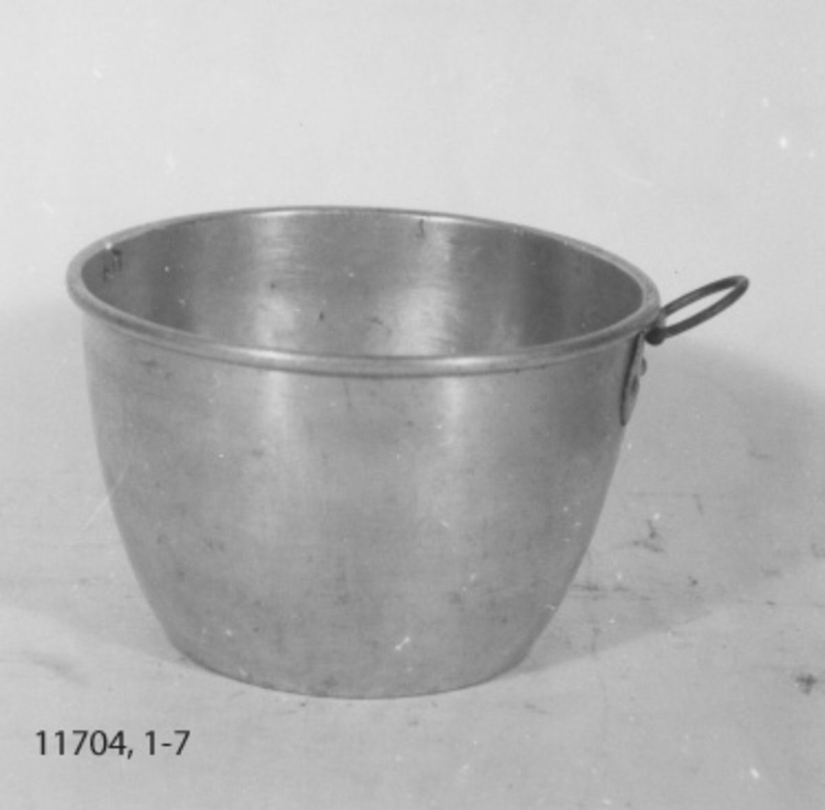Matskål, djup. Av aluminium. Har formen av en upp- och nedvänd stympad kon. På yttersidan är en ring fastnitad. Märkt med kronstämpel.