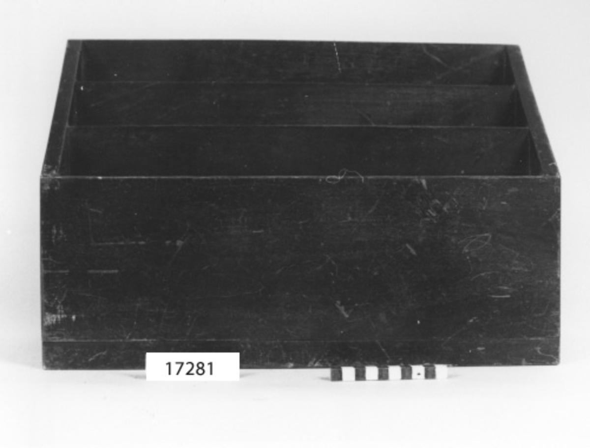 Rektangulär förvaringshylla av betsad och fernissad mahogny. Hyllan utgörs av bottenplatta, ett bakstycke med högsta höjd (300 mm) och ett lägre framstycke (H = 165 mm). Sidostycken samt hyllfack, två stycken, anpassas i höjd till fram- och bakstyckena, så att det främsta facket har den lägsta höjden. Sinkade kanter, bottenplattan fäst med mässingsskruv.
