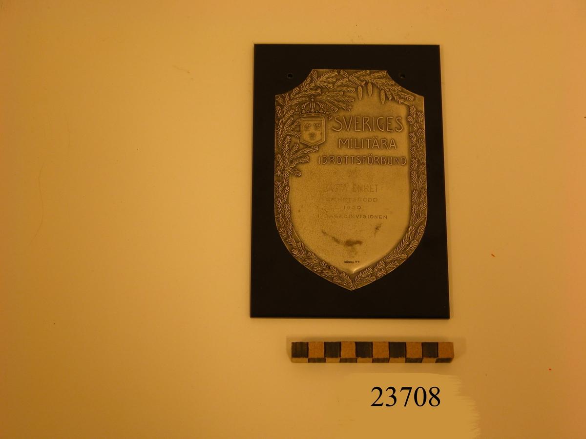 Plakett av silver i form av vapensköld fäst på platta av bakelit. Längs sköldens kant dekor föreställande granris samt tre hängande grankottar. I sköldens övre vänstra hörn en liten vapensköld med tre kronor, krönt med kunglig krona. Text på plaketten: SVERIGES MILITÄRA IDROTTSFÖRBUND BÄSTA ENHET ENHETSRODD 1950 1 JAGARDIVISIONEN. Se SSS och X pärm.