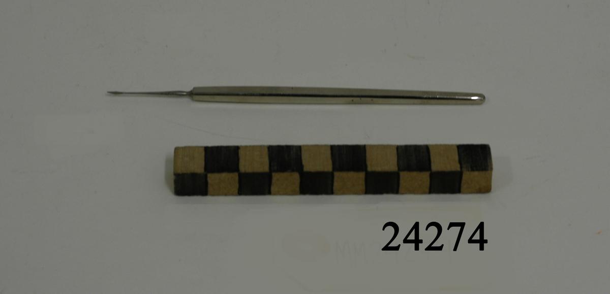 """Tunn, rak, platt lansettformad operationskniv av rostfritt stål. Tveeggat knivblad. Blankt fyrkantigt skaft. Text i godset: """"STILLE""""."""