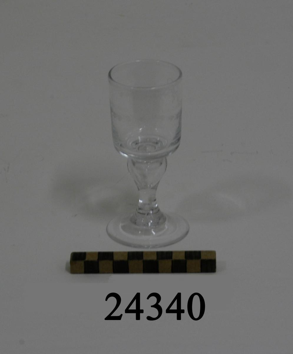 Handblåst snapsglas, rakt, cylinderformat på fot. Längs glaset slipning: två paralella linjer samt tre nedåtgående bågar med stiliserade blad och två stycken rosetter. Etsat emblem: ett krönt stockankare omgivet  av tågvirkeslinga. Benet runt och blåst med bubbla. Rund plan fot.
