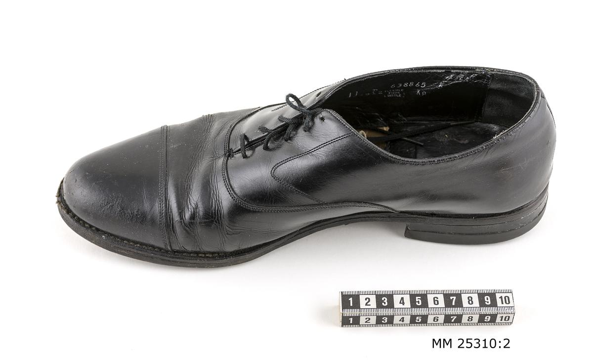 """Lågskor från jagaren Halland. Sko av svart läder med slät form samt mönster av dubbla sömmar. Svart gummiklack. Snörning framtill med svart textilsnöre som träs i fem par hål. Svart läder i skornas insida. Sulans undersida märkt: """"The Florsheim shoe"""". Skons insida märkt med diverse nummer: 638865 5 KA."""