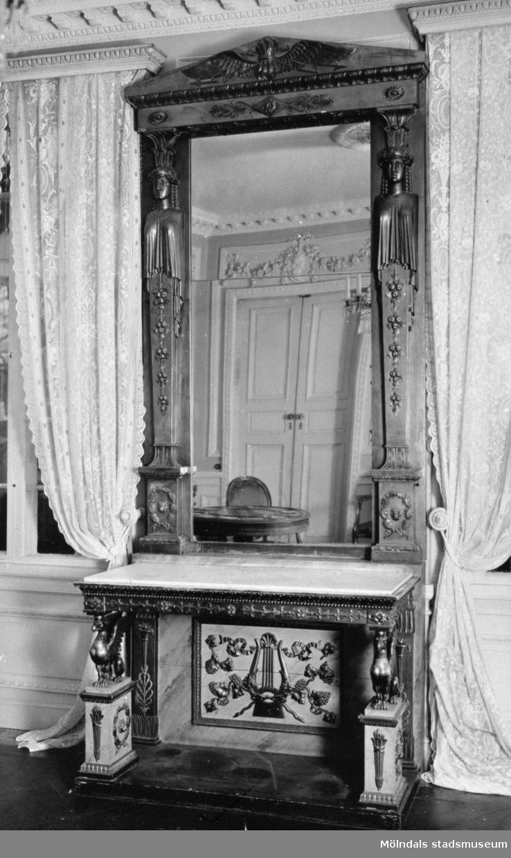Hög, avlång och dekorerad spegel som står ovanpå ett dekorerat bord. Pjäsen är placerad mellan två fönster. I spegelglaset ses en dubbeldörr med girlangrelief ovanför. Östra förmaket på Gunnebo slott, 1930-tal.