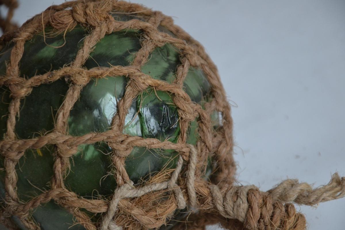 En grønn glasskule med nett av kokostau festet rundt seg. En hempe av kokostau er festet i den ene enden. På glasskula er merket bokstavn M. Nettet er tvinnet på plass, ikke knytt.