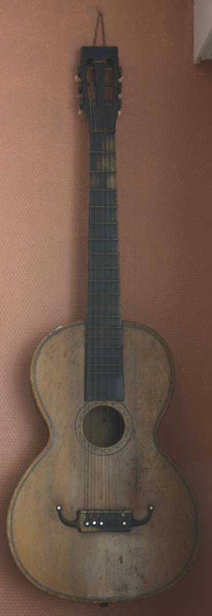 Laget av tre, lyse brun farge på framsiden, mørkere brun på sidene, baksiden mørke brun. Rundt hele gitarkassen to smale og en bredere strek i mørkebrun farge. Rundt hullet i gitaren i mørkebrun strek ytterst, innenfor denne litt mønster. 6 stålstrenger. Mål gitarkasse: Lengste punkt 45 cm, bredeste punkt 31 cm, høyde 8 cm. Lengde gitaren: 95 cm.