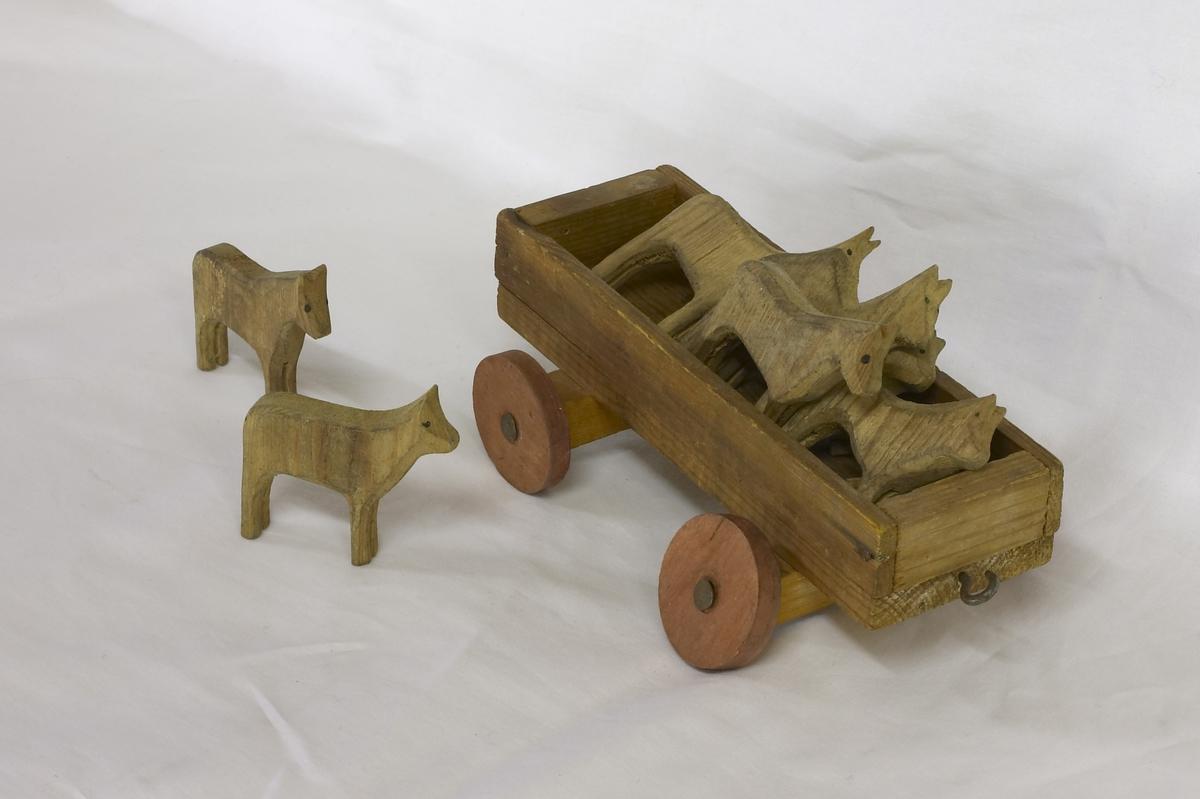 a) Lekehus, b) lokomotiv og 3 vogner, c) lekehest. 7 utskårne sauer og en gris i tre. Ett puslespill med 6 klosser i tre med pålimt motiver i papir.