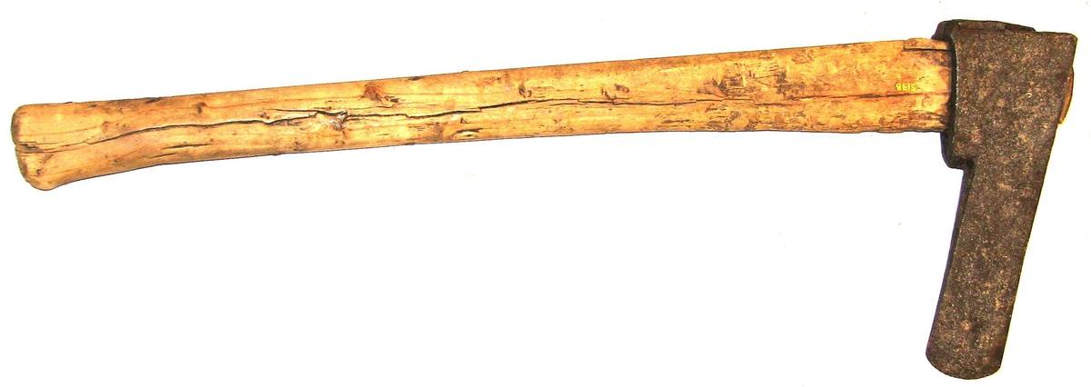 """1 boløks (hulhugningsøks)  En boløks fra Valdres. Kaldes nu ogsaa """"hulhugningsøks"""". Øksebladet er tykt kileformet og fra øiet til eggen omtrent jevnbred 4,8 cm. Øksebladets længde er 13,5 cm, og øksens samlede længde 22 cm. Skaftet er 63 cm langt. Hjemmesmidd øks av meget gammel type. Den anvendes nu kun til at hugge hul i tømmerstokken, før benyttedes den ogsaa til fælding av trær. Kjøpt ved lensmand Eivind Berg, Østre Slidre, Valdres."""
