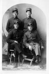 Studioportrett av fire soldater i helfigur.