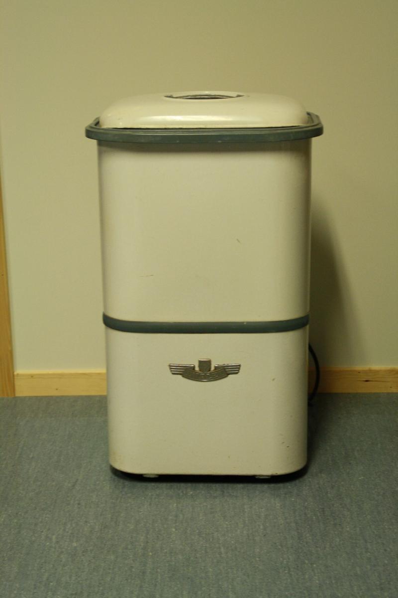 Evalet vaskemaskin frå 50-talet. Enkel rektanguler med låk. Laust låk med kikkehol i. Maskina har eit enkelt hjul som driver vatnet rundt og ei plastsil. Utløp i botn. Rør til vatn går ut av maskin bak. På baksida er det også ein brytar.