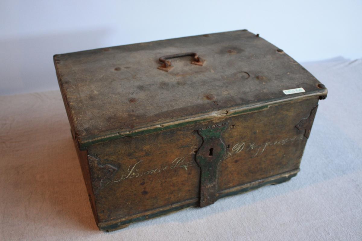 Kiste med hank i topp av metall. Metallbeslag på kantane og over lås.Kista er låst og det manglar nøkkel. Spor etter grønmaling til dekor i øvre og nedre kant. Namn til eigar av kista skreve inn i framme.
