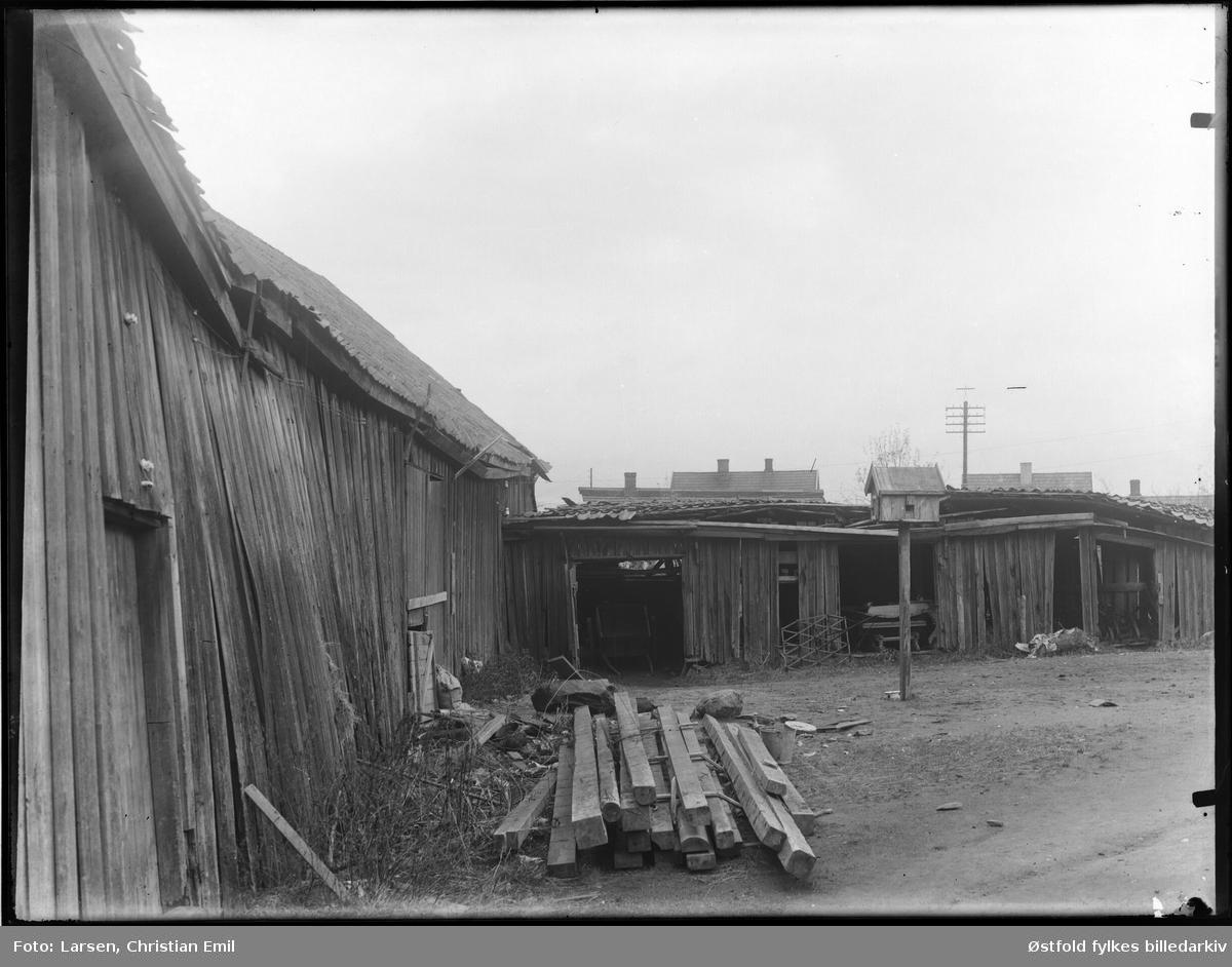 Bakgård med uthus, materialstabel,, og dueslag, ant i Sarpsborgdstriktet. Ukjent sted.