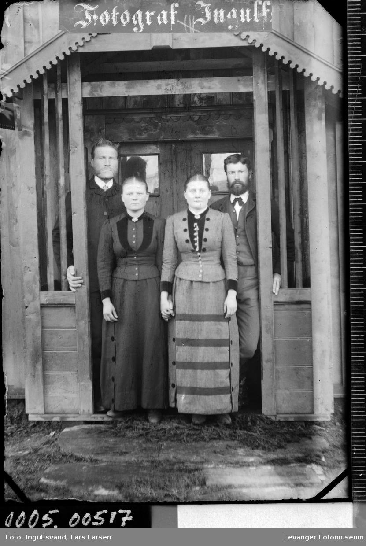 Gruppebilde av to kvinner og to menn i et inngangsparti.