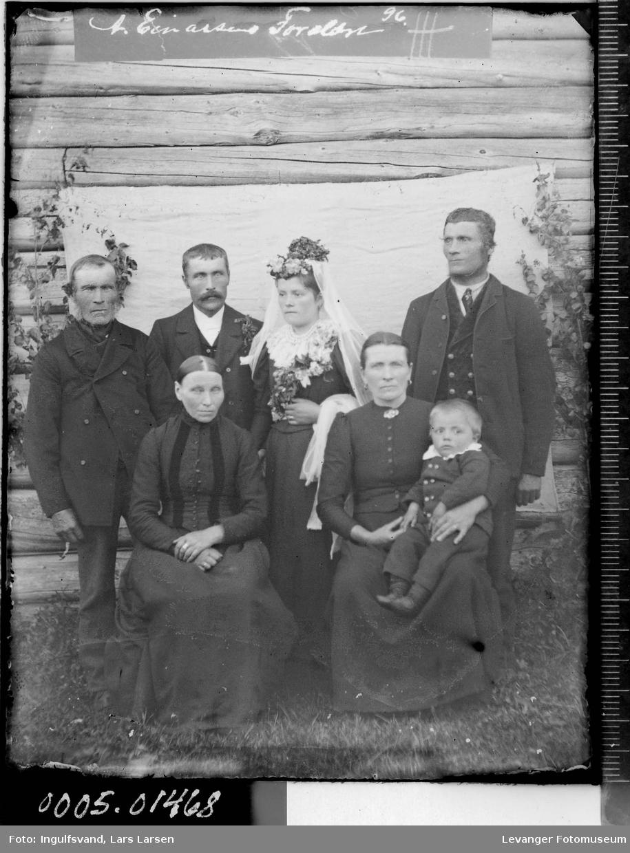 Gruppebilde av et brudepar, to menn, to kvinner og et barn.