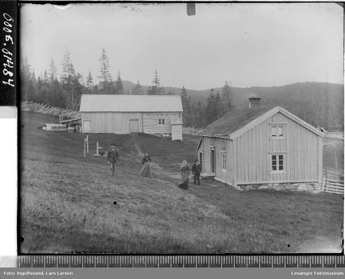 Gårdsbygninger med to kvinner og to menn ved siden av.