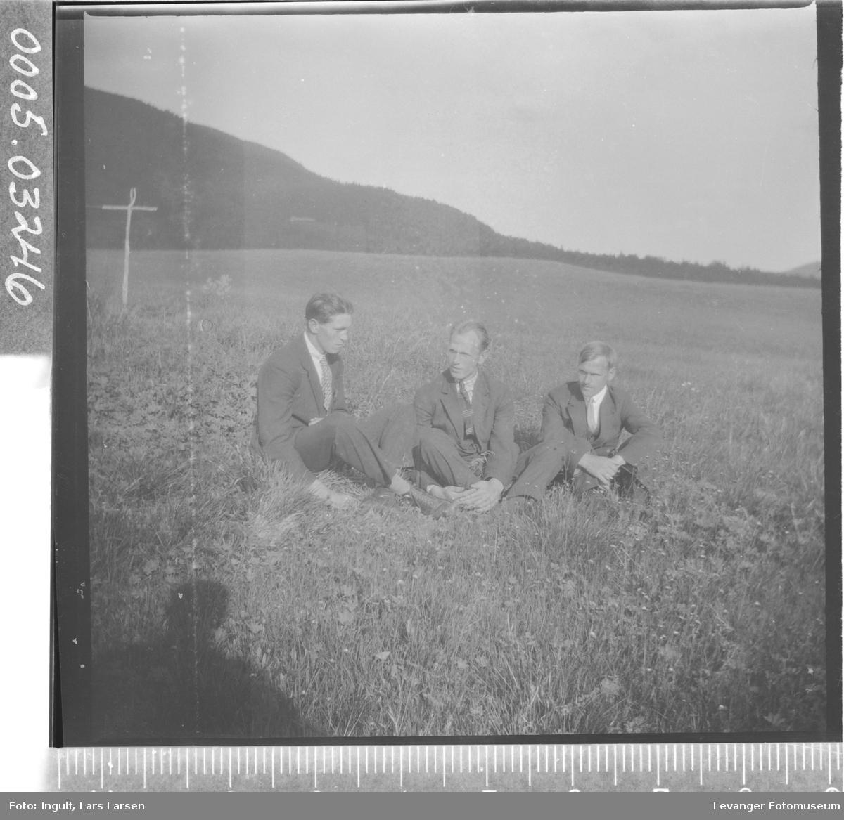 Gruppebilde av tre menn som sitter i en eng.