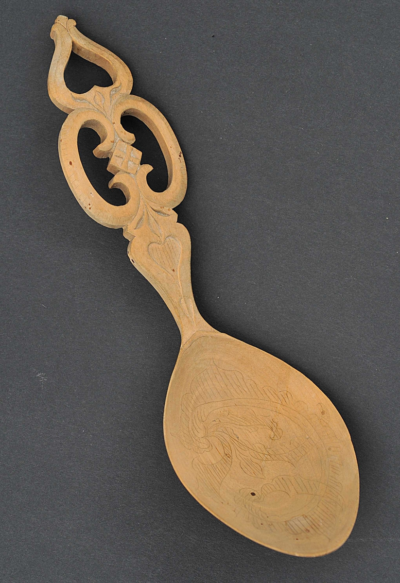 Kolroser i skeibladet. Handtaket har hjarteforma dekor både i gjenombroten og utskoren form.