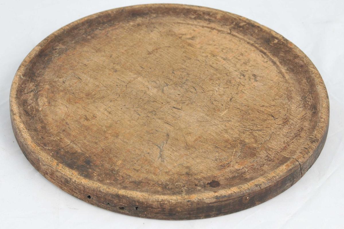 Sirkelrund, flat tallerken av tre. Ytre kant er svakt opphøga med djupare rand med rille innanfor. Likt utforma på begge sider.I kanten på den eine flatsida er det skore inn ein bokstav.