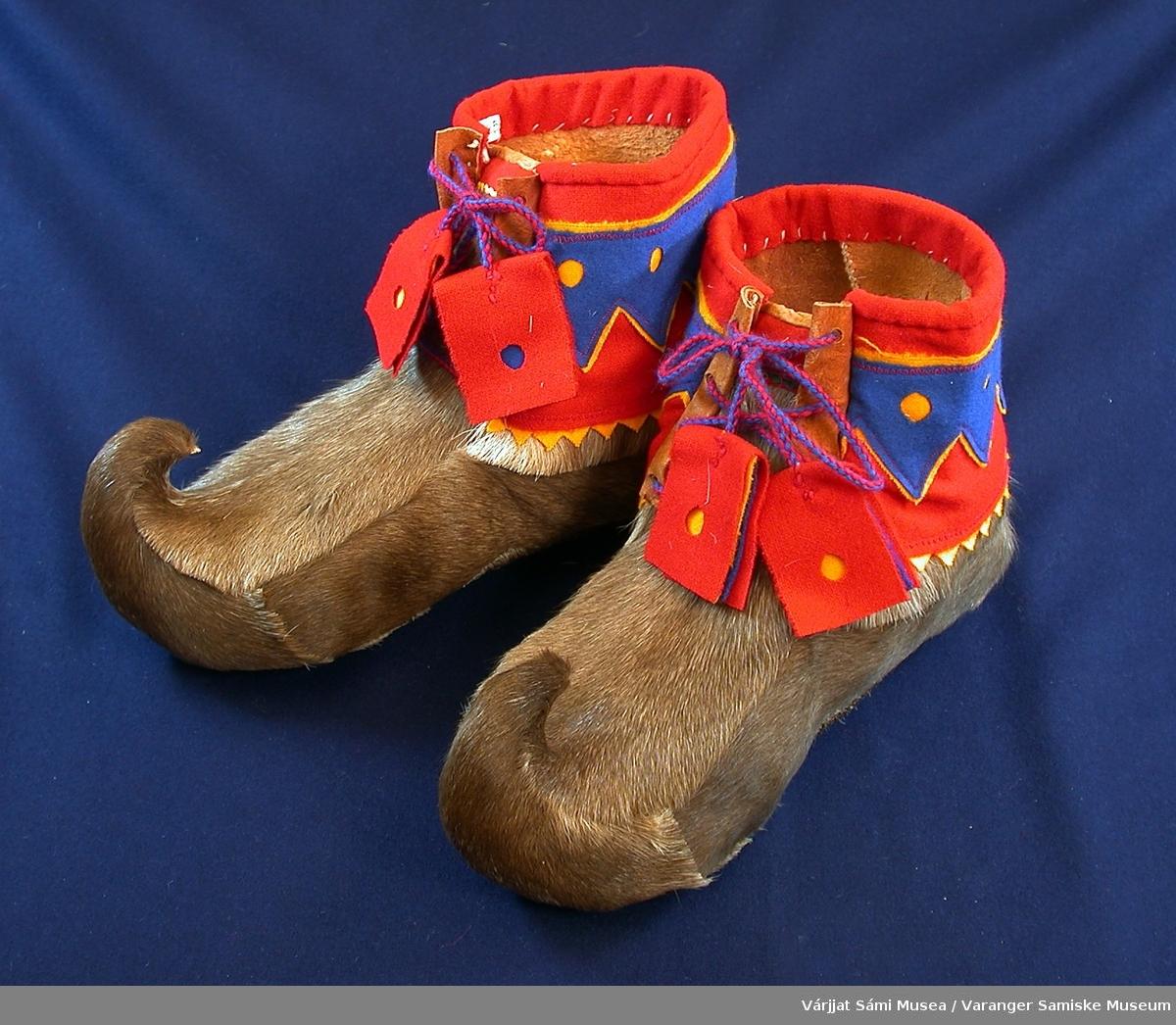 Et par herreskaller med snøring av brunt leggskinn av rein. Ankel-delen av skallene er dekorert med klede i rødt, blått og gult i sik-sak-mønster. Foran er det åpning med snøring. Snøringen er flettede snorer av rødt og blått ullgarn.