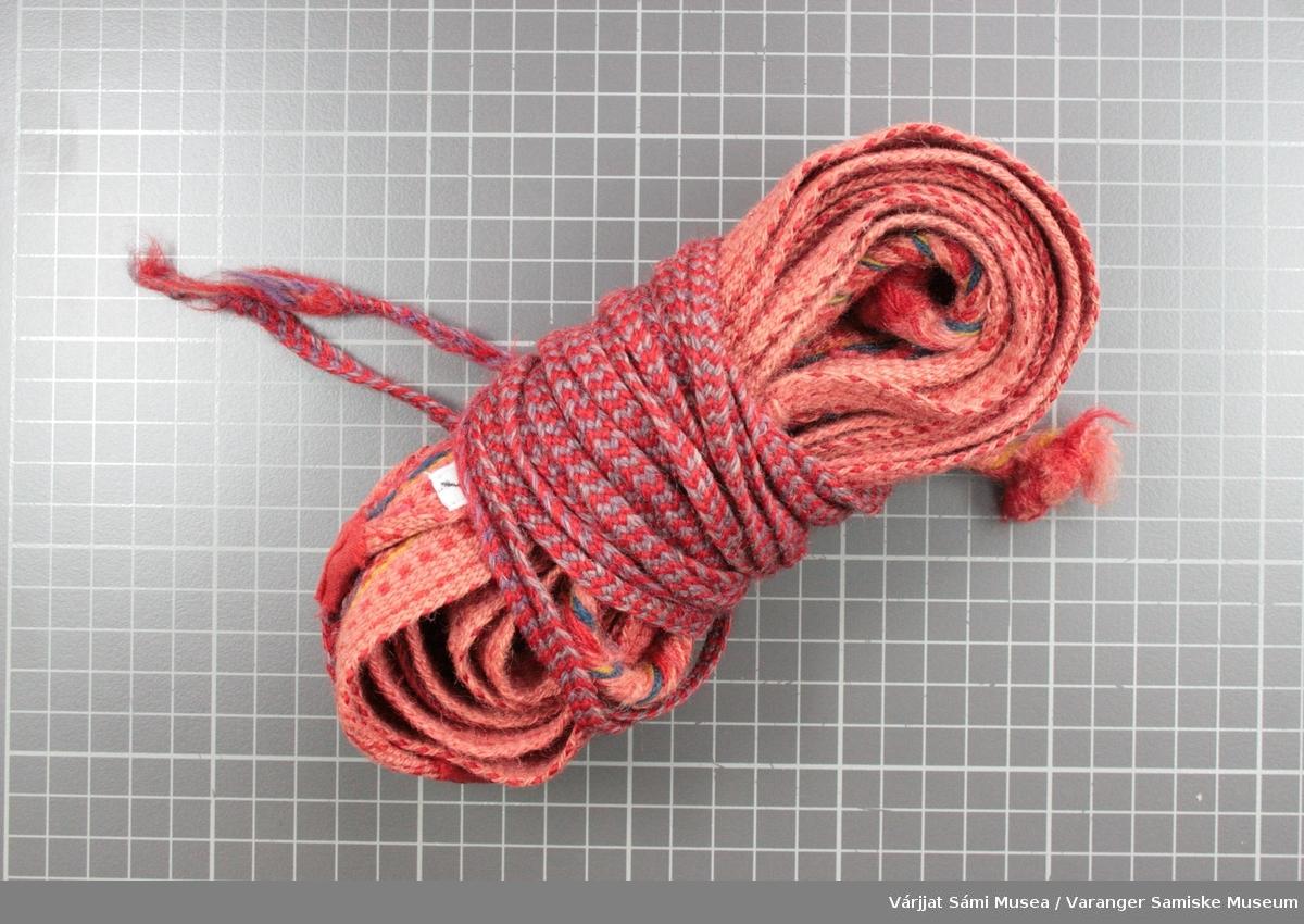 Et par grindvevde dameskallebånd, røde kanter med langsgående striper i mørkere rød, i midten er det langsgående gule striper og blått sikksakk mønster. Den røde bunnfargen er svært falmet og er nærmest rosa, men de røde mønstertrådene er ikke falmet og er tydelige mot den rosa bunnfargen.  Kort flette av renningstrådene i den ene enden, til å feste båndet i fottøyet,   Bárggeš dvs. lang flette av rødt og blått ullgarn, til å surre rundt leggen og feste båndet i den andre enden av skallebåndet.