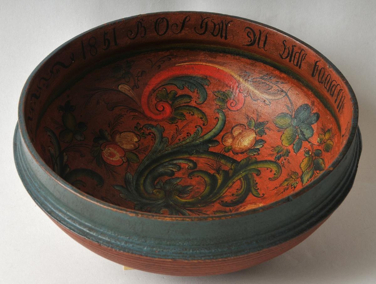 Ølbolle med raud botnfarge og blågrøn rand øvst utvendig. Rosemåling innvendig og skriftrand rundt kant. Målinga er typisk Mevastaul, eit godt arbeid.