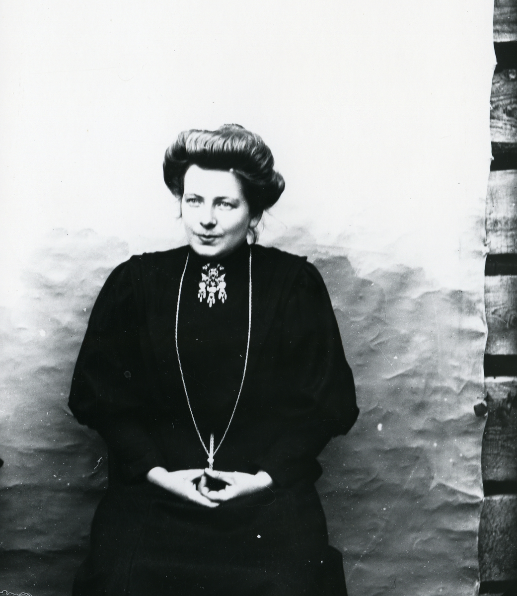 Mørkkledd kvinne i halvfigur, sittende foran lerret