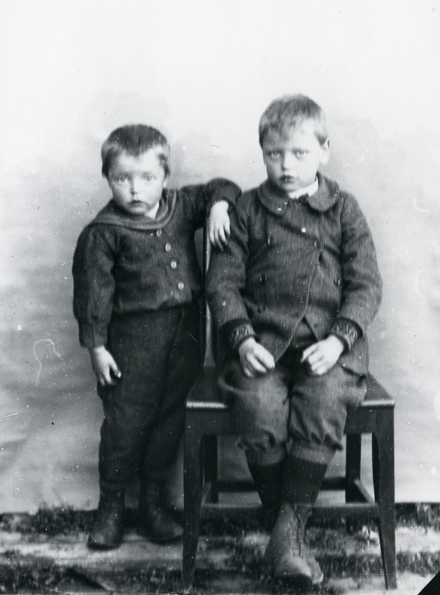 To gutter fotografert med lerretbakgrunn, den ene sittende på stol