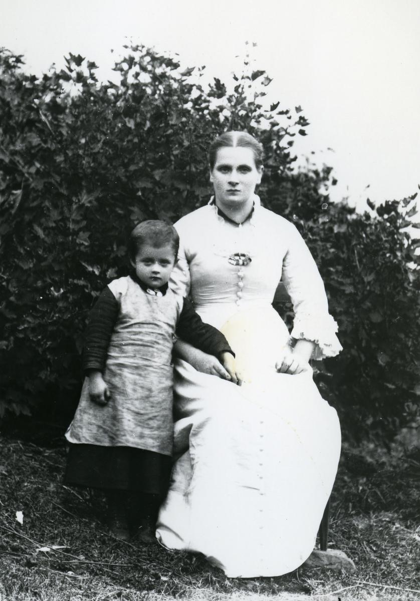 Kvinne med barn, lauv og lerret i bakgrunnen