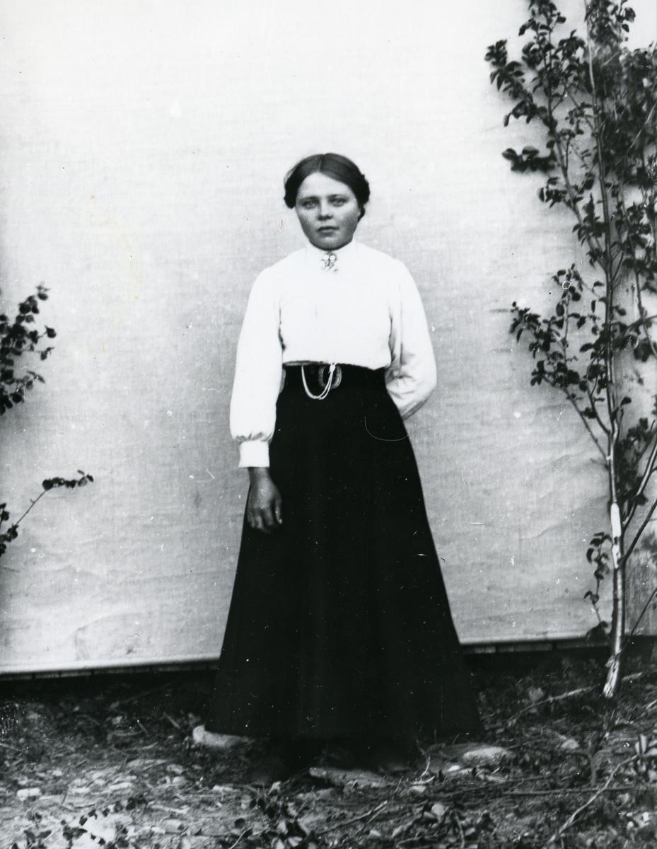 Kvinne i helfigur, stående foran lerret med løvkvister