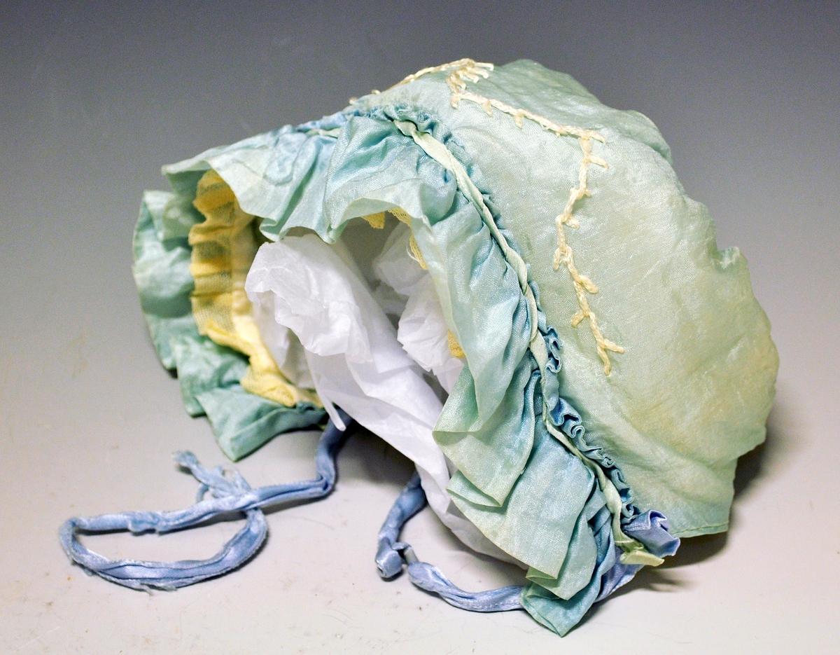 Lyseblå  lue i silke med kant foran i folder. Påsydde knyttebånd på hver side.Dekorbroderier i hvitt siksak mønster. Luen er sydd i ett stykke tøy og rynket sammen bak rundt en rund form. Luen er fôret med hvitt silketøy og det er sydd på en smal blonde foran innvendig. Luen er falmet.