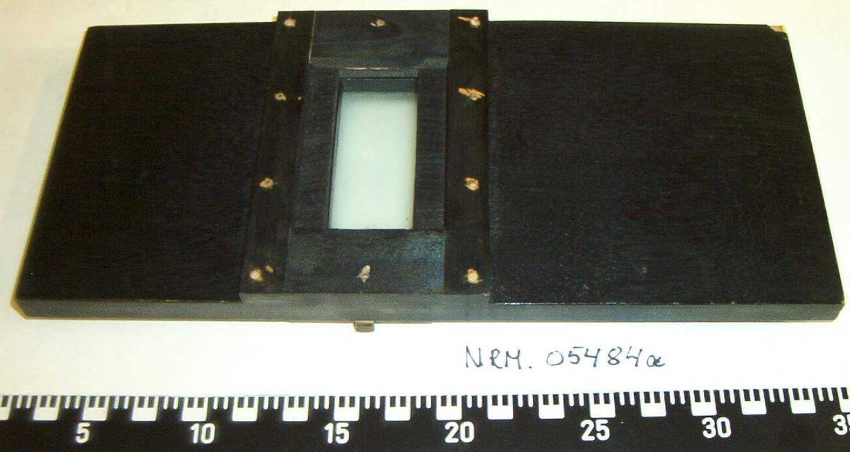 Fotoapparatet har fire føtter, en i midten og tre ut til sidene. Dreiehjul i metall på siden som kan dreies for å heve og senke kameraet. To fotokasser i tre og med linser. Fotoplate med linse medfølger.