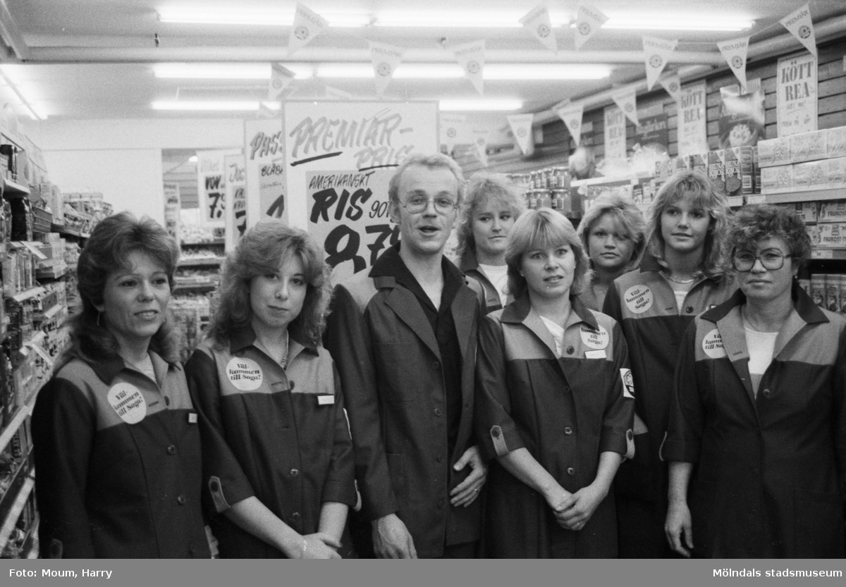 """Livsmedelsaffär nyöppnar i Bölet i Kållered, år 1984. """"Lars Lundgren i kretsen av nyanställda ungdomar tycks ta öppnandet med en sång på sina läppar.""""  För mer information om bilden se under tilläggsinformation."""