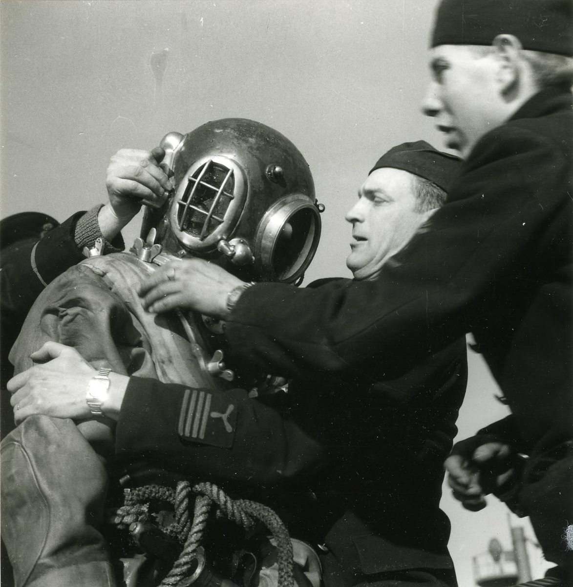 Utrustning av dykare på ubåten Sjöormen vid Skeppsholmen 1949. Hjälmen sättes på.